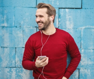 man blij haar baard koptelefoon lachen rode trui